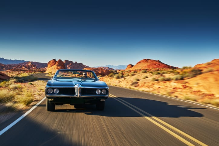 man driving vintage car through desert